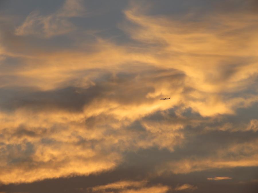 夕焼けの空を飛ぶ飛行機