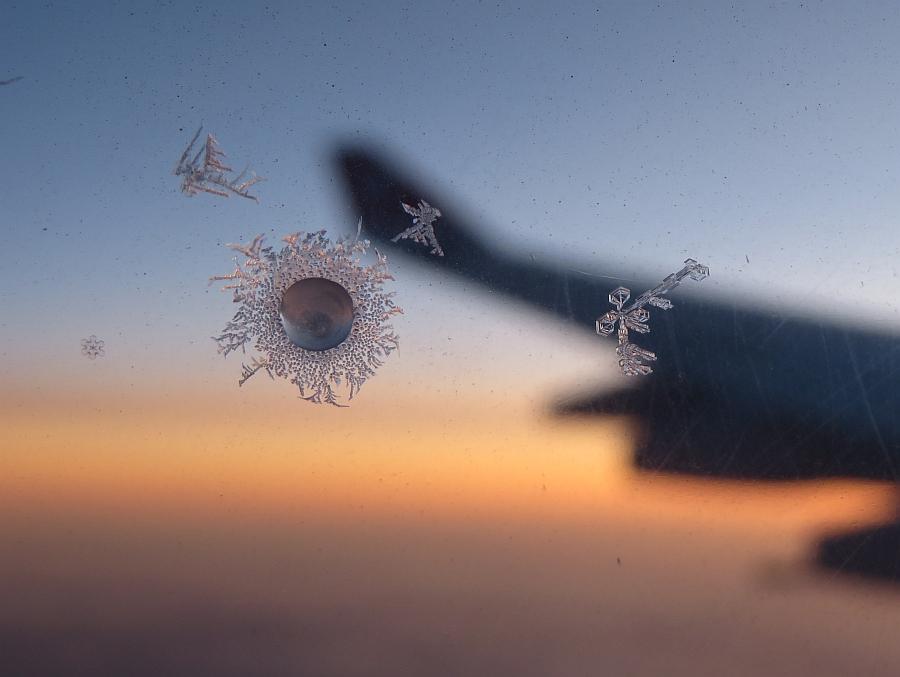 飛行機の窓にできた氷。夕日を背景に。